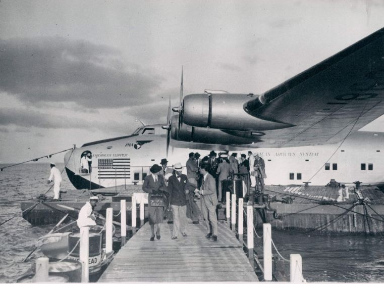 1940 customers deplane in Lisbon fromBoeing B314 American Clipper, registration NC18606 while ground crew unload customer luggage from the bow hatch.