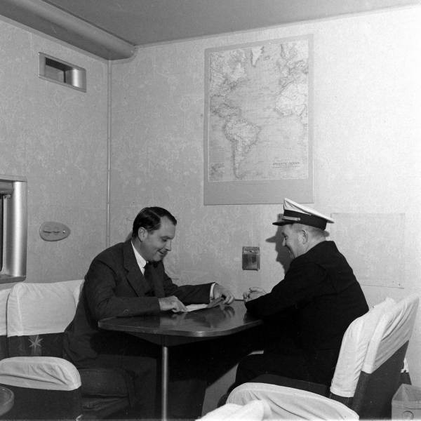 1941 Pan Am founder JuanTrippe sitting in the main lounge  of a Boeing B314 in discussion with a pilot