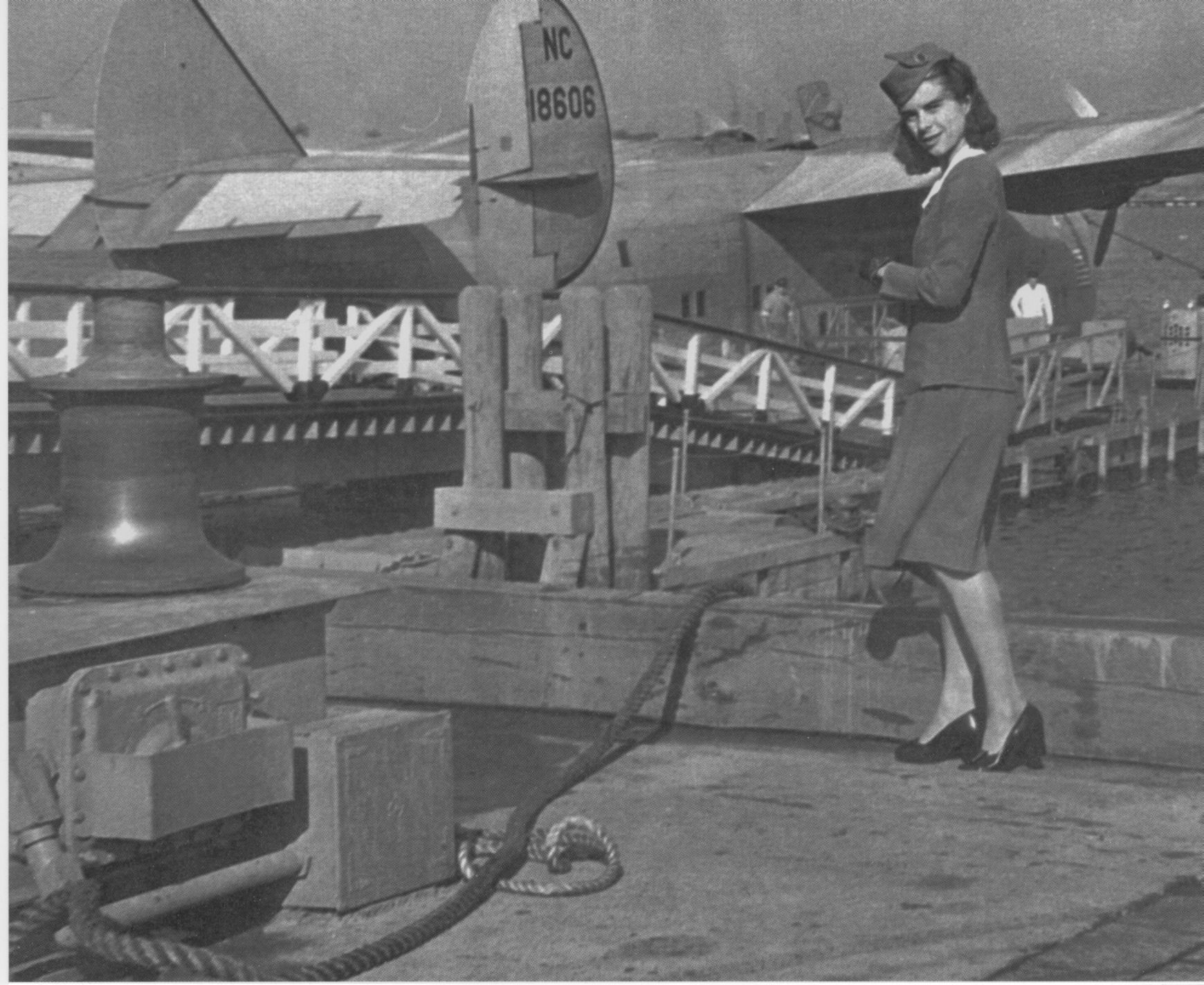 1945 Stewardess Lotta Westerhortsmann posing with Boeing 314 flying boat at the dock