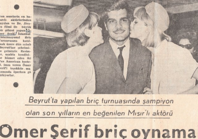 1960s Judy Skartvedt & another Flight Attendant pose for a publicity shot with actor Omar Sherif for a Turkish Newspaper.  Judy is on the right facing the photo.