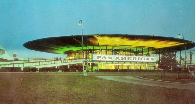 1960s A twilight shot of the Pan Am WorldPort Terminal at New York JFK airport.  Aircraft parked nose in so the extended roof could protect passengers from rain & snow.  The idea for this design came from Berlin's Tempelhof Airport that offered passengers a completely covered ramp area.