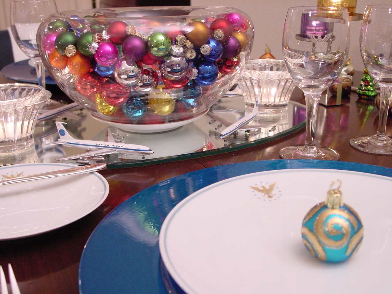 The 1960s Pan Am 'President' pattern is used with bright blue chargers and colorful holiday glass balls in this table setting.