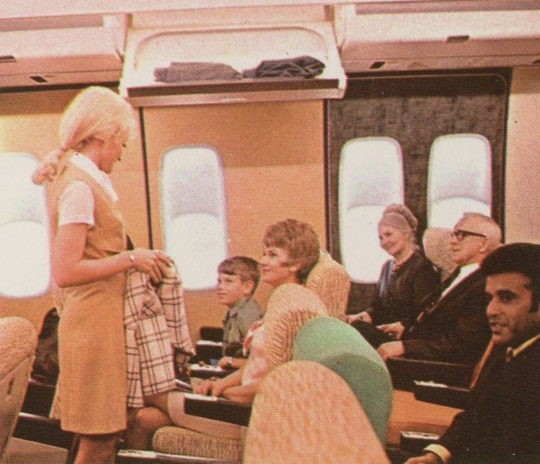 1970 A Flight Attendant in the Galaxy Gold uniform speaks with customers in the economy cabin of a mock up 747.