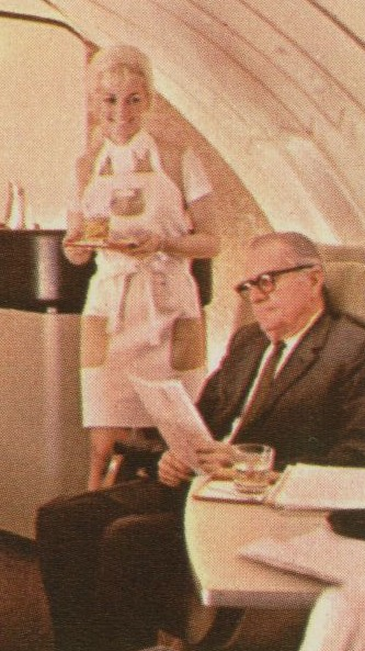 1970 A Flight Attendant wearing an apron to match her Galaxy Gold uniform serves customers in a mock up of a 747 upper deck lounge.