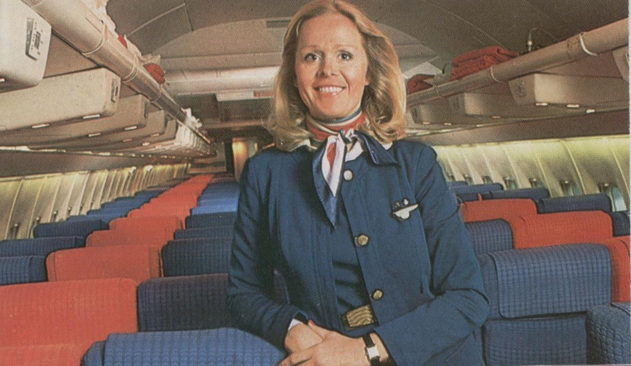 1970s A Flight Attendant in a uniform designed by Edith Head stands in the aisle of a Pan Am 707 reconfigured for charter service with 180 economy seats.