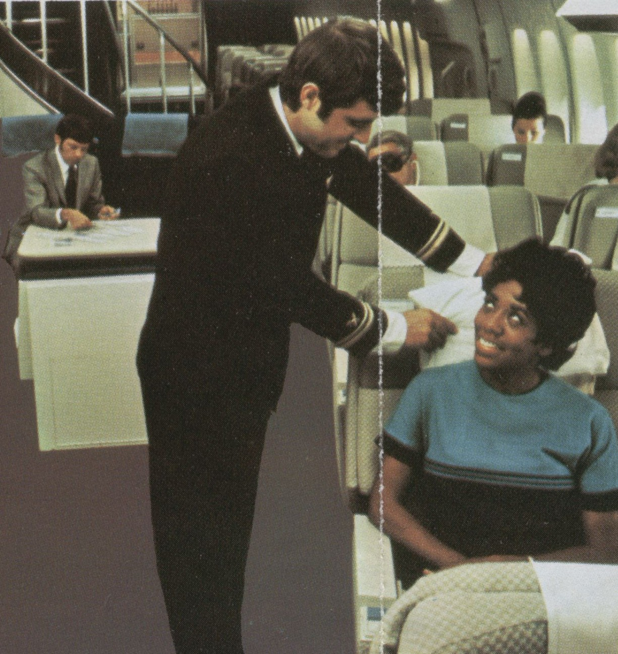 1970s  A Pan Am steward assists a customer in the First Class cabin of a Boeing 747.