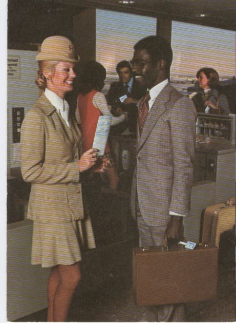 1970s A Flight Attendant in a Galaxy Gold uniform greets a boarding customer at Pan Am's WorldPort at New York, JFK Airport