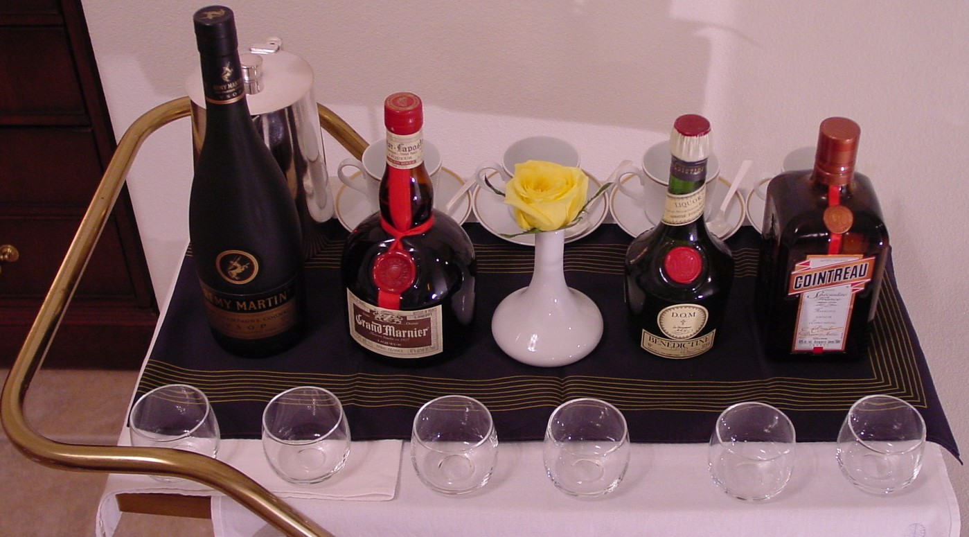 An after dinner liquor cart using 1970s economy class wine glasses is presented on the cart.