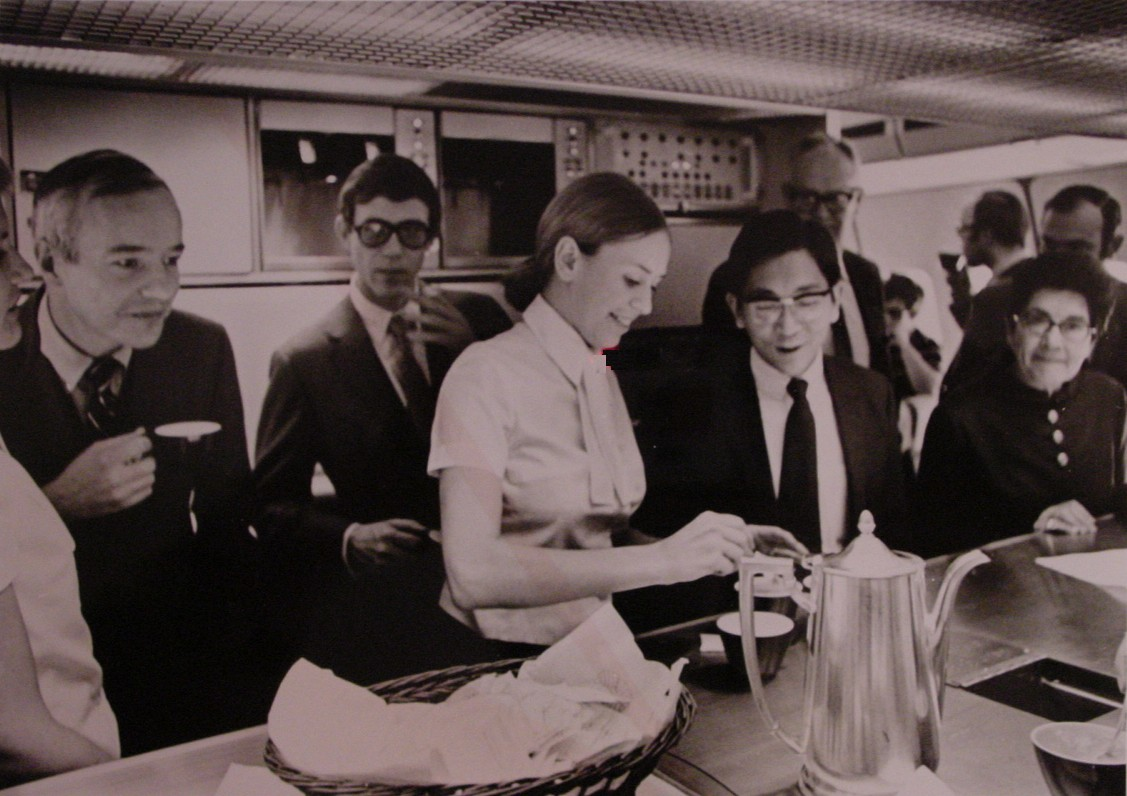 1970s A flight attendant pours coffee in the main galley of a Pan Am 747.  These passengers are members of the Press on an publicity flight.