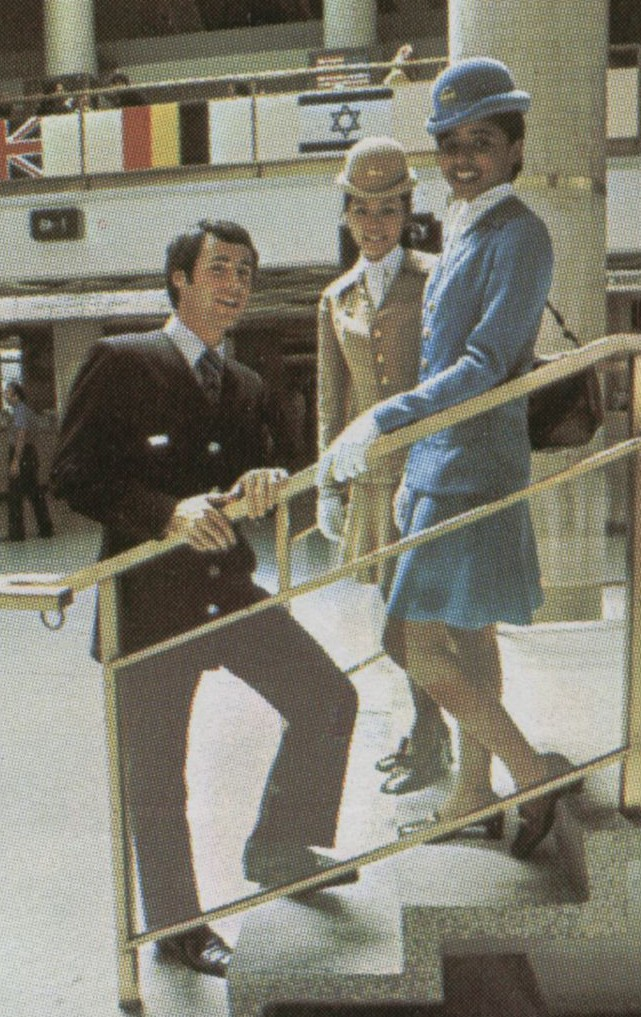 Early 1970s  two female flight attendants and thier male counterpart pose on steps leading to the upstairs restaurant at Pan Am's New York, JFK