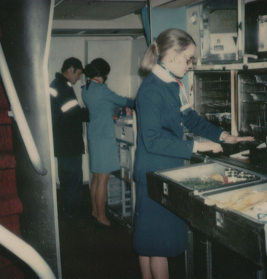Dec 1976  A  flight attendant in navy blue prepares the first class galley of a 747 prior to customer boarding.  In  the background the  flight attendant in the light blue uniform demonstrates a broken galley shelf to a mechanic.