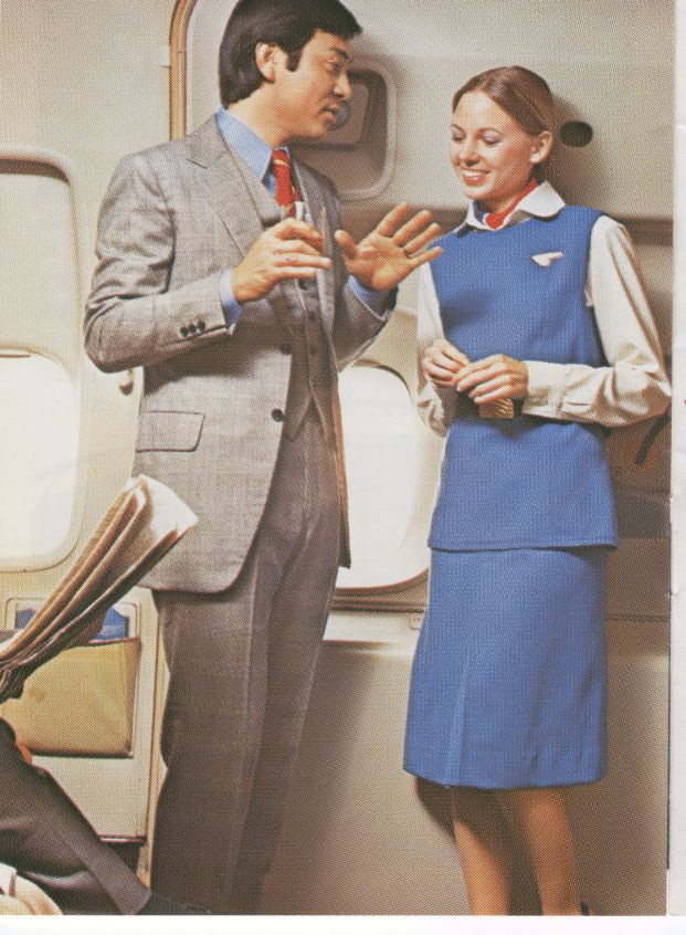1976 A flight attendant speaking with a customer in the foyer of a 747 doorway.