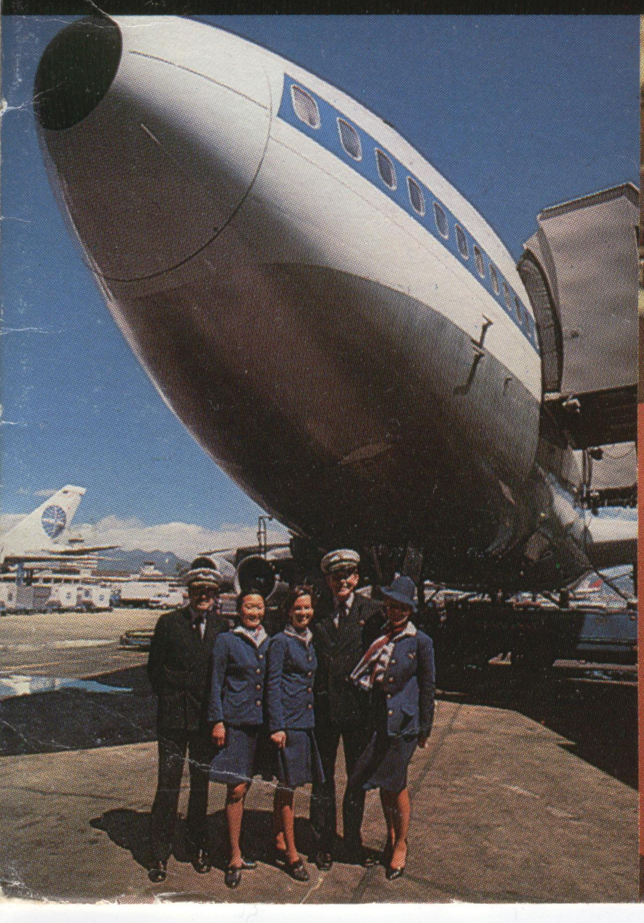 1977 Some Pan Am crew members pose by the nose of a 747 at the gate in San Francisco with the mountains in the background.