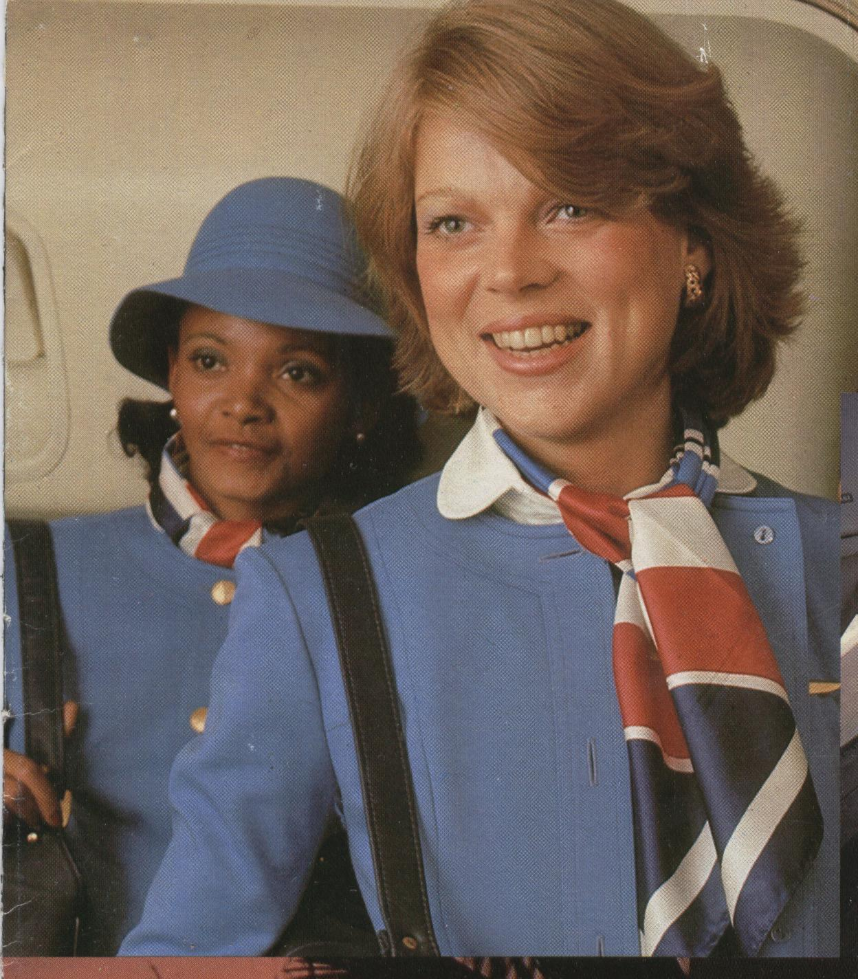 1977 Pan Am flight attendant Jennifer Andrews (left) and colleague pose in the doorway of a 747.  Their uniform was designed by Hollywood costume designer, Edith Head and introduced in 1975.