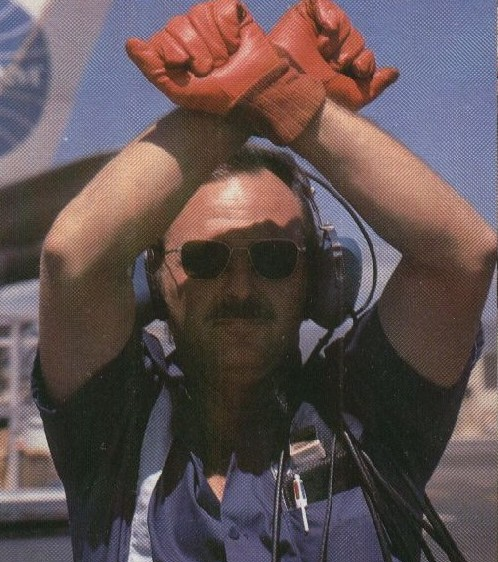 1977 A Pan Am mechanic parks an airplane wearing a pair of bright red gloves.