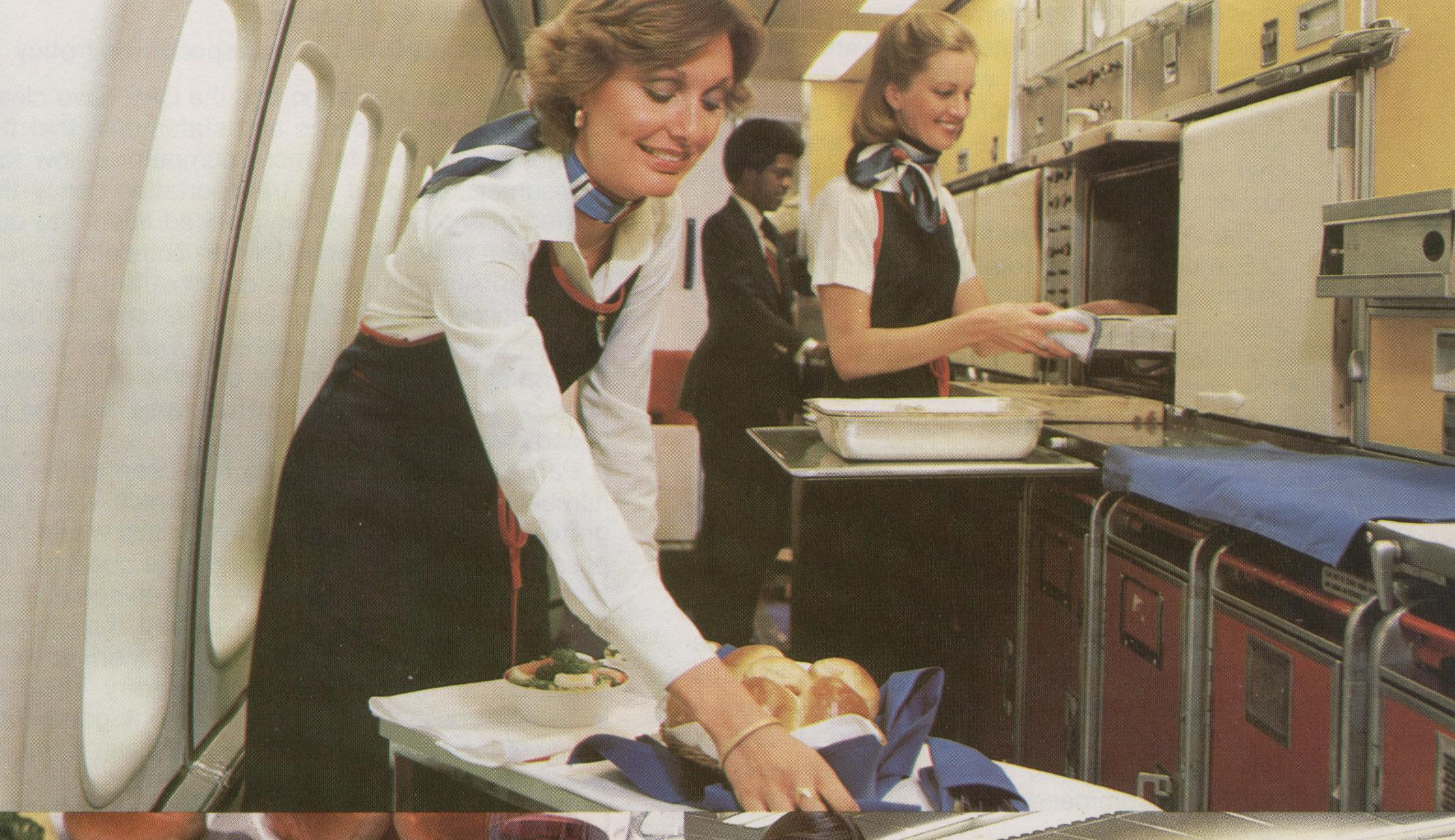 1977 Crew members prepare a meal in the galley of a Pan Am Boeing 747SP.  Sue Smith prepares the cart.  Judy Skartvedt is standing by the open oven and  Antonio Gooding is working at the rear of the galley.