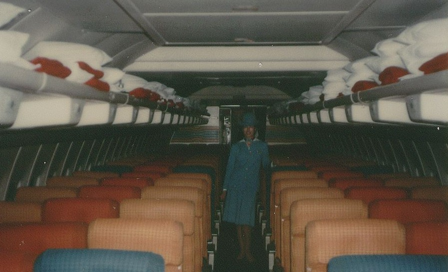 Dec 1978 A Pan Am flight attendant poses in the economy section of a 707 tail number N886PA at Washington Dulles Airport.