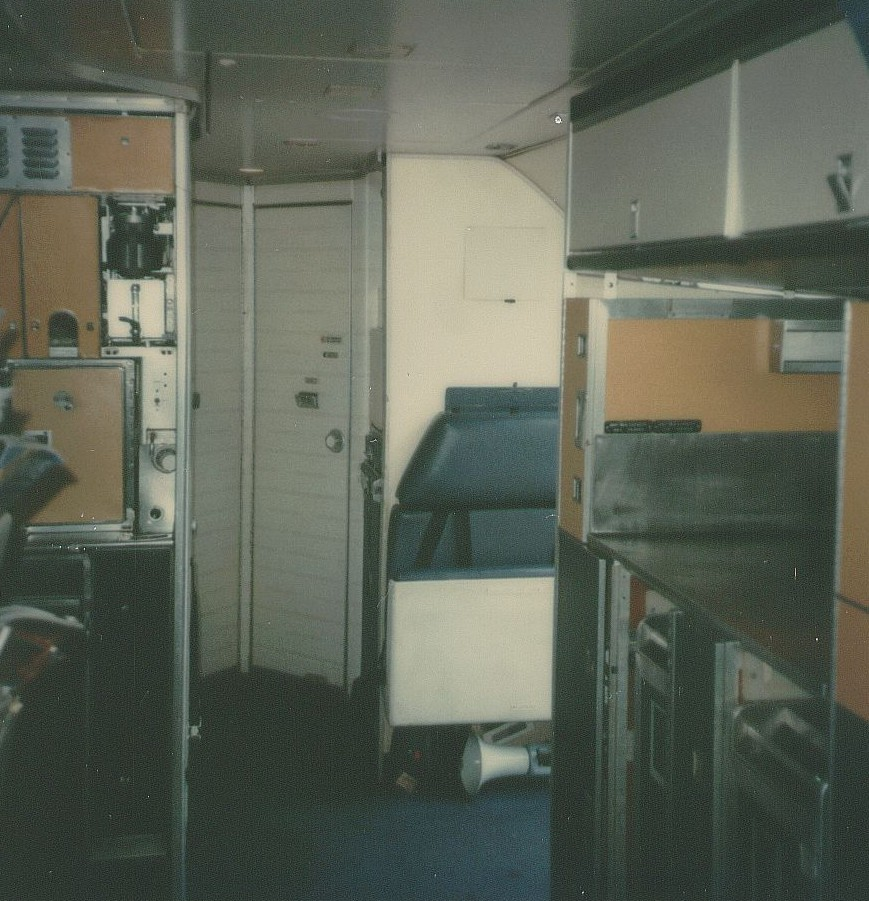 May 1979 The rear service area of a Pan Am Boeing 707.  In the far back are lavatory doors.  In the middle on the right is a folding crew jumpseat by the rear passenger door.  In the forward rigth is an auxiliary galley placed across from the main rear galley which can be partially seen in the forward left.  The auxiliary galley was needed for  the all charter configuration which featured 180 economy seats.