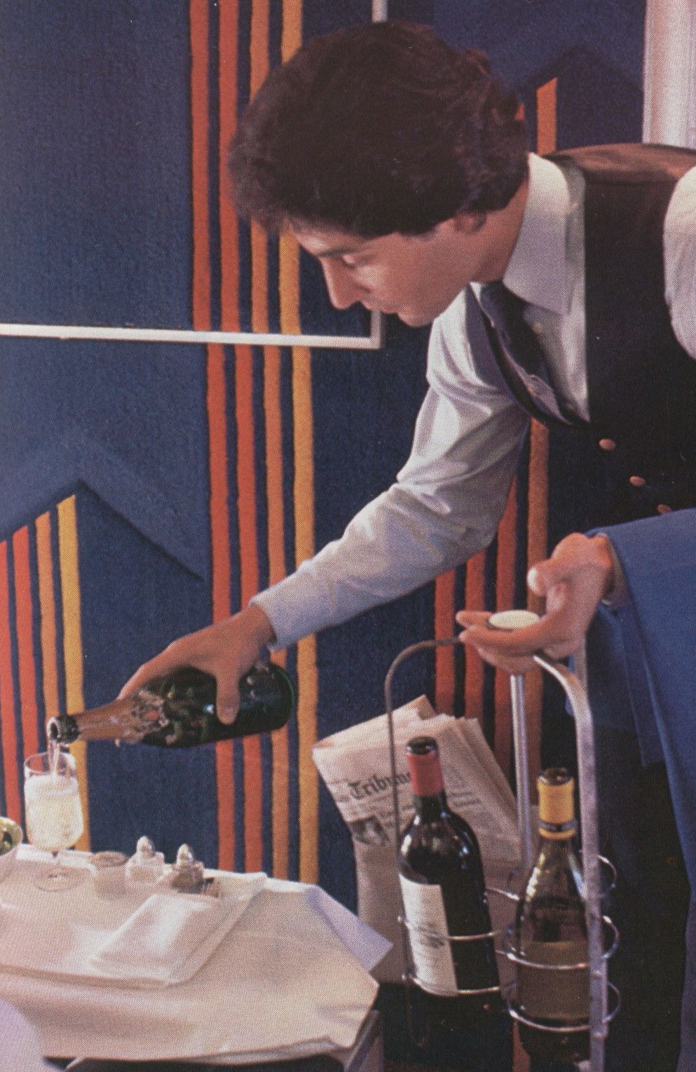 1980 A Pan Am flight attendant carries both red and white wine as well as champagne to offer each First Class customer their choice.