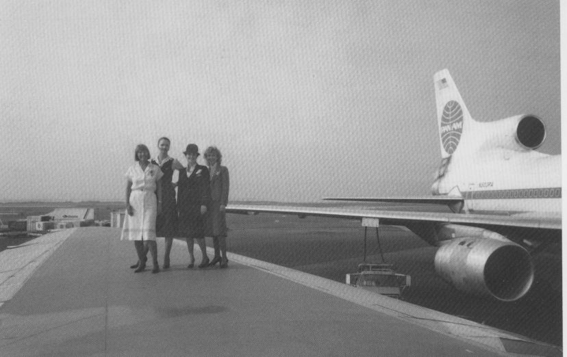 1980s Four Pan Am Flight Attendants pose on the wing of a Lockheed L1011-500.  One Flight Attendant is wearing the summer dress that was available in white & powder blue for several years in the early 1980s.  The uniform was designed by Adolfo and introduced in July of 1980.