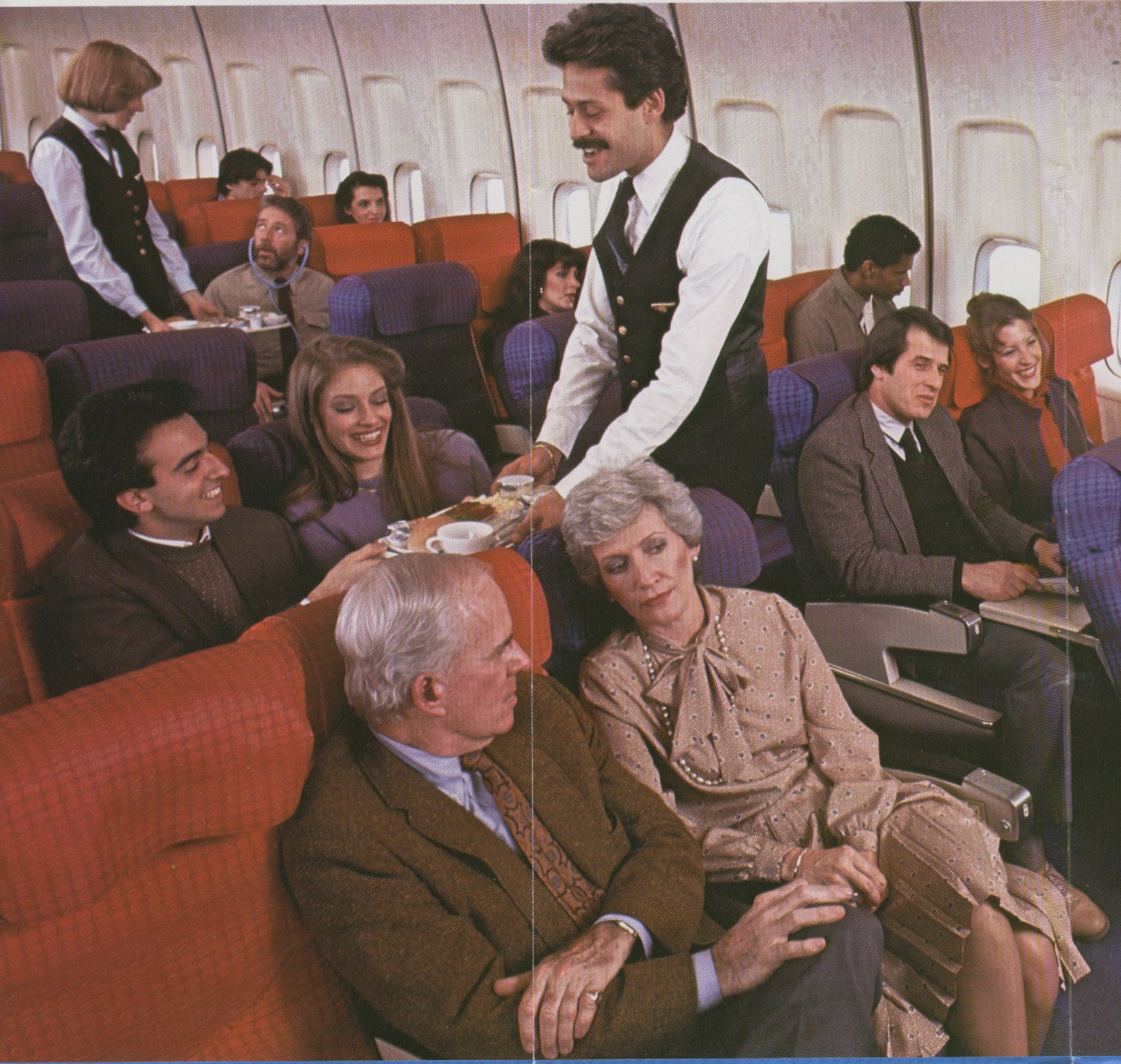 1980s The economy section of a Pan Am 747 during meal service.  The male flight attendant is Carlos Rosalino.