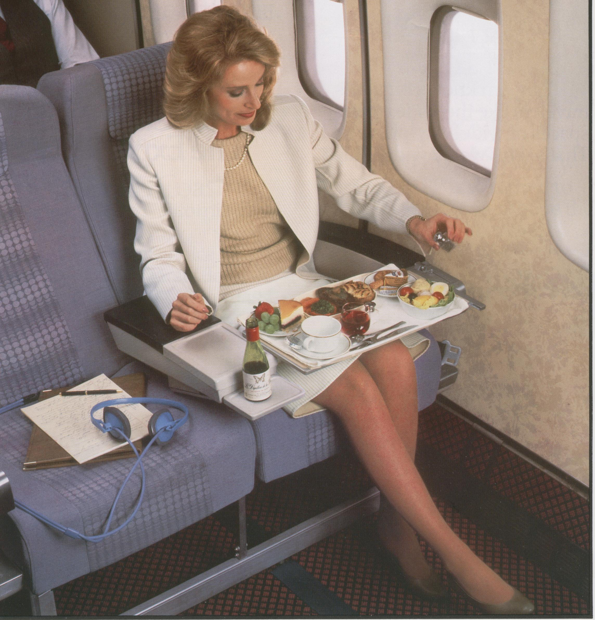 1980s A customer enjoying a meal in Pan Am's Clipper Class (business class) on a Boeing 747.  Pan Am's first Clipper Class Cabins offered 8 across seating instead of the 10 across in Economy class.