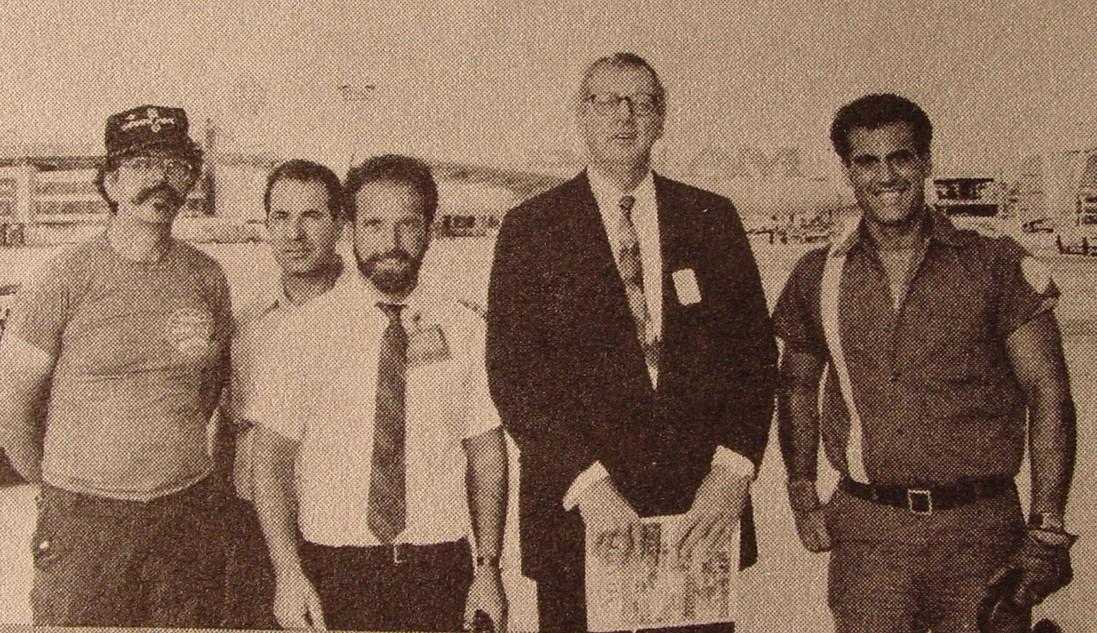 1980s  Pan Am Chairman C. Edward Acker (tall with glasses) visits with ground staff members Angelo Klunich (left with mustache) John Jamatta (with beard & tie) and Al Hernandez with single stripe shirt on the left of Ed Acker at the Pan Am Shuttle at LaGuardia Airport in New York.