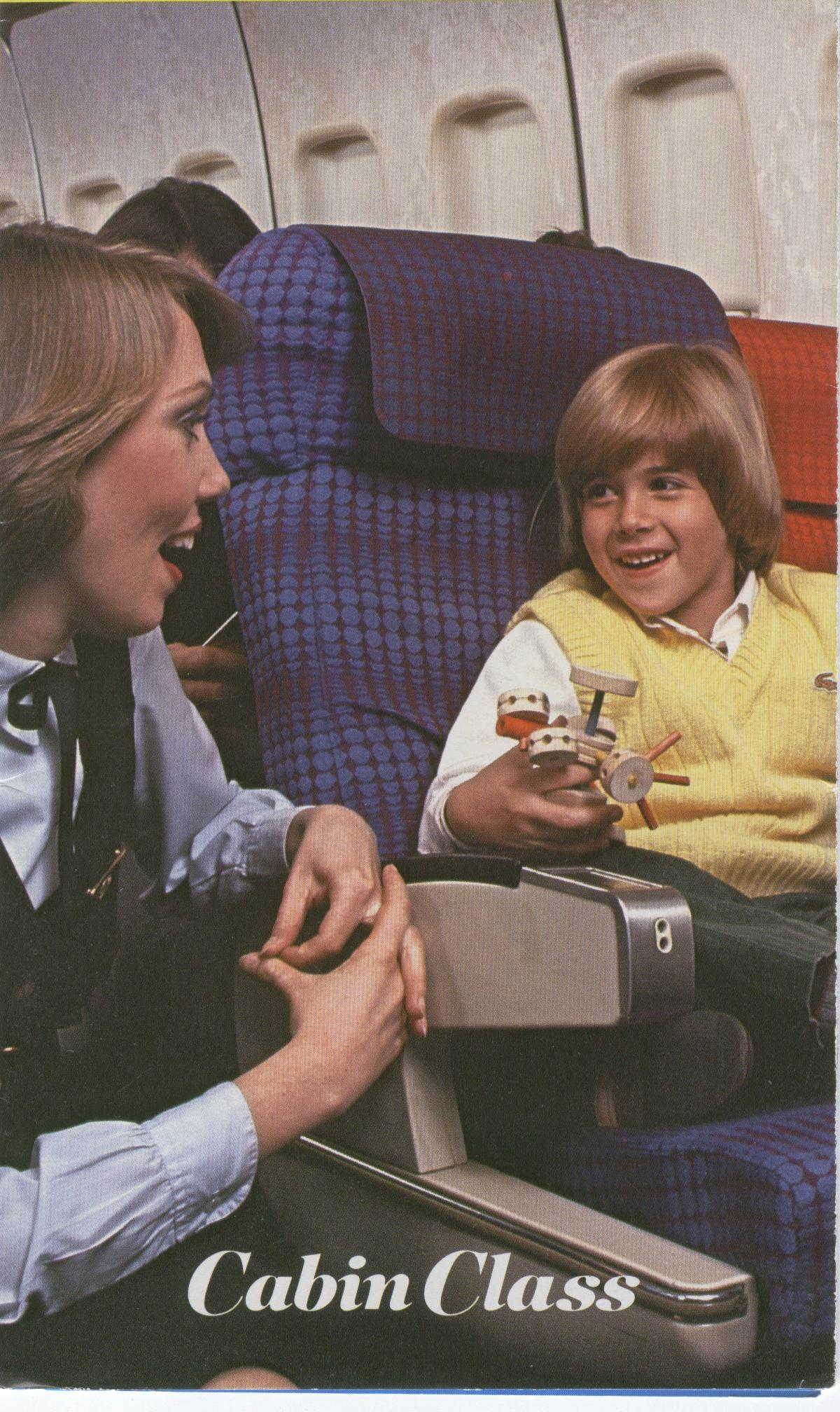 1980s A Pan Am Flight Attendant speaks with a young customer in the economy section of a 747.