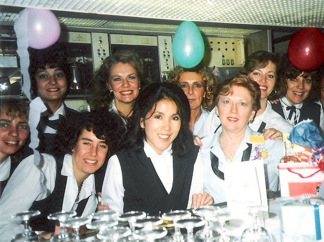 1980s Purser, Peggy Catalano,(wearing a yellow rose) on her last working flight before retirement poses in the Economy Class galley of a Pan Am 747 with fellow crew members.  Judy Skartvedt is standing behind Peggy with hands on Peggy's shoulders.