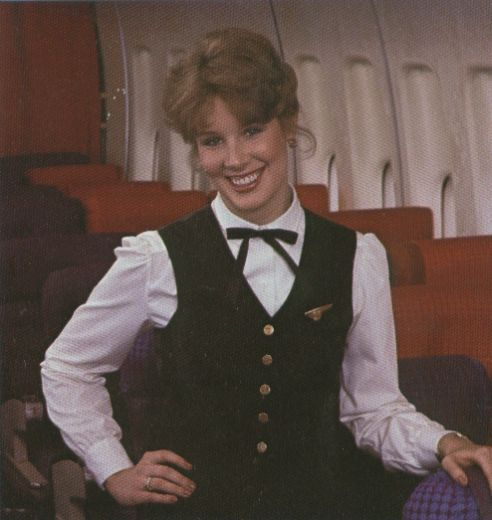 1980s A Pan Am Flight Attendant poses in the economy section of a 747.