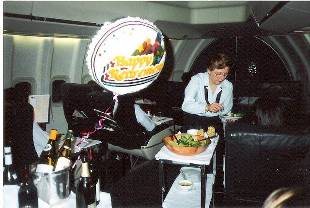 1980s Purser, Peggy Catalano, begins her last roundtrip from New York to Rome before retiring.  The crew tried to make this trip as memorable as possible  with balloons & banners on board.  Here Peggy serves salad from the cart in the First Class Cabin of a Pan Am 747 en route to Rome.