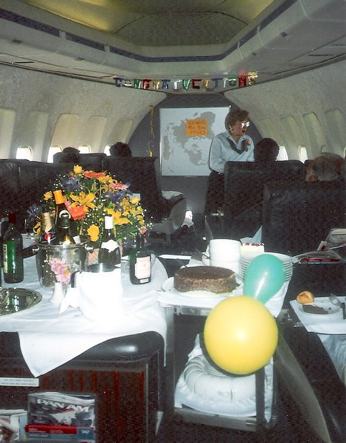 1980s Purser, Peggy Catalano, on her last working flight before retirement.  The crew threw a party in-flight from Rome to New York complete with balloons and banners.  Here Peggy is seen offering dessert from the cart in the First Class cabin of a Boeing 747.