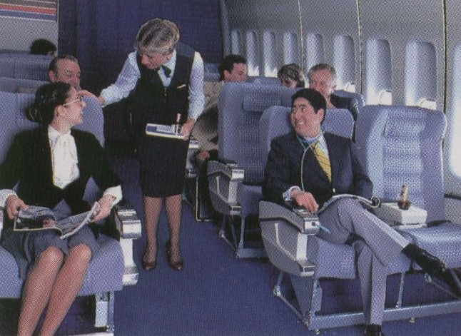 1980s A flight attendant assiting a customer in an early version of the Clipper Class (business class) cabin  with 8 across seating.