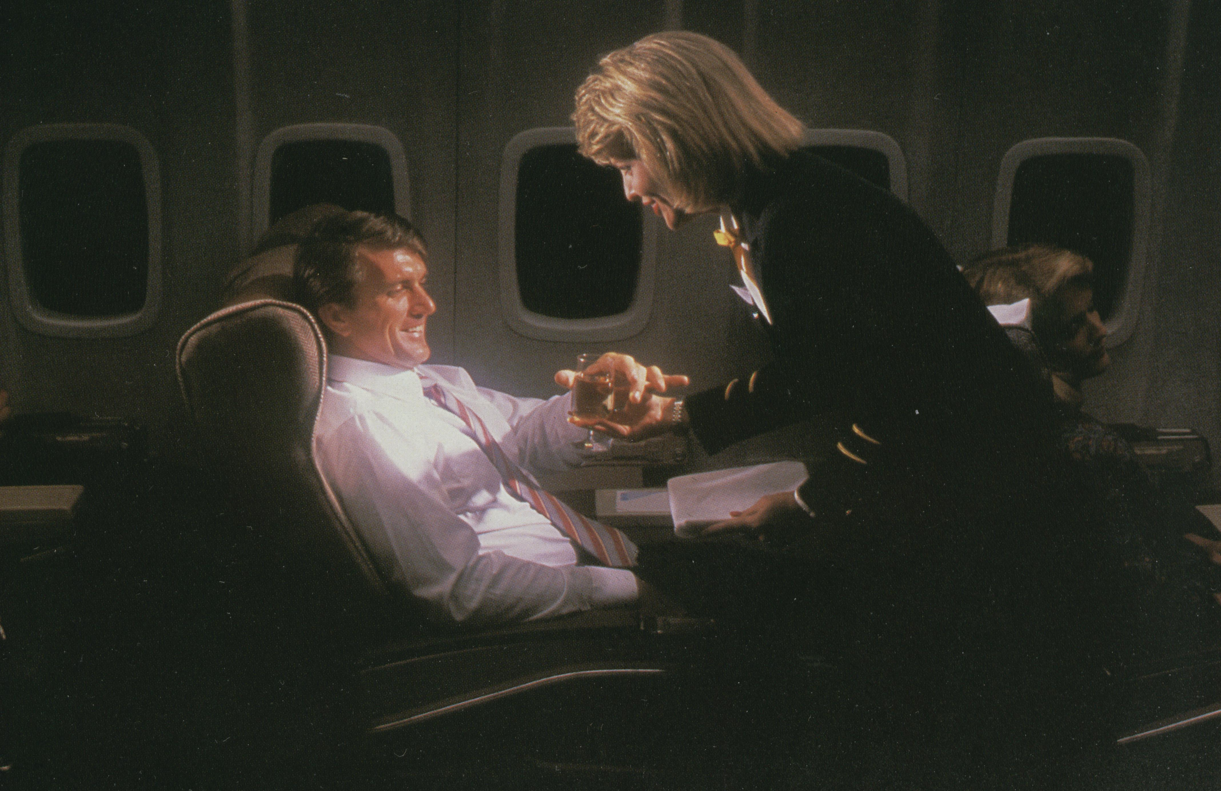 1980s A flight attendant serves a Clipper Class (business class) customer on an overnight flight.