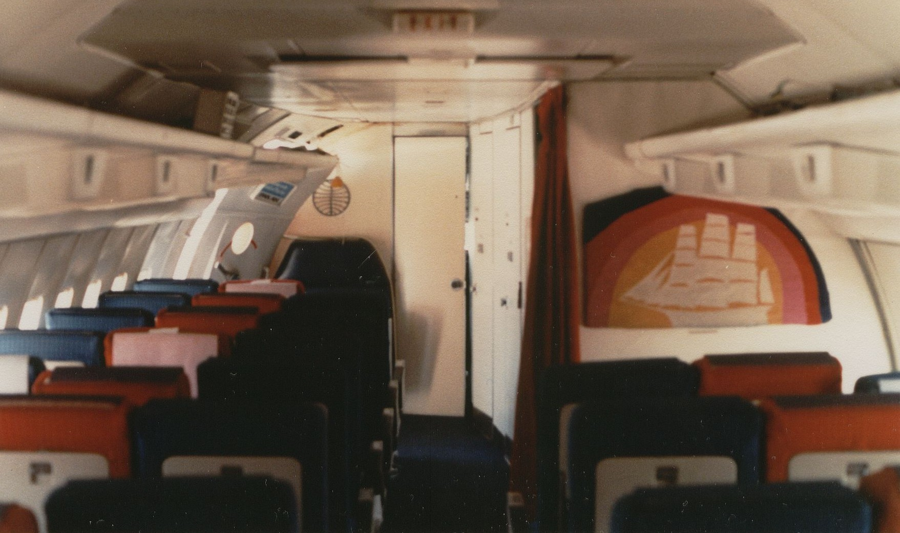 August 1981 The forward cabin of a Pan Am Boeing 707 in an all economy configuration with 180 seats.  In front of the Clipper Ship bulkhead artwork is the forward galley and two lavatories.  In the front center isthe door to the cockpit and to the left the passenger door.