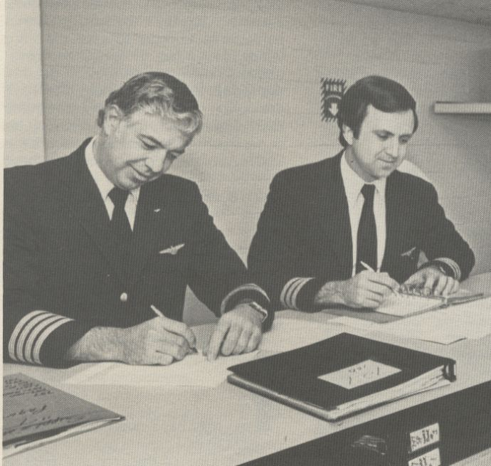 1981 Pan Am pilots prepare pre-flight paperwork.