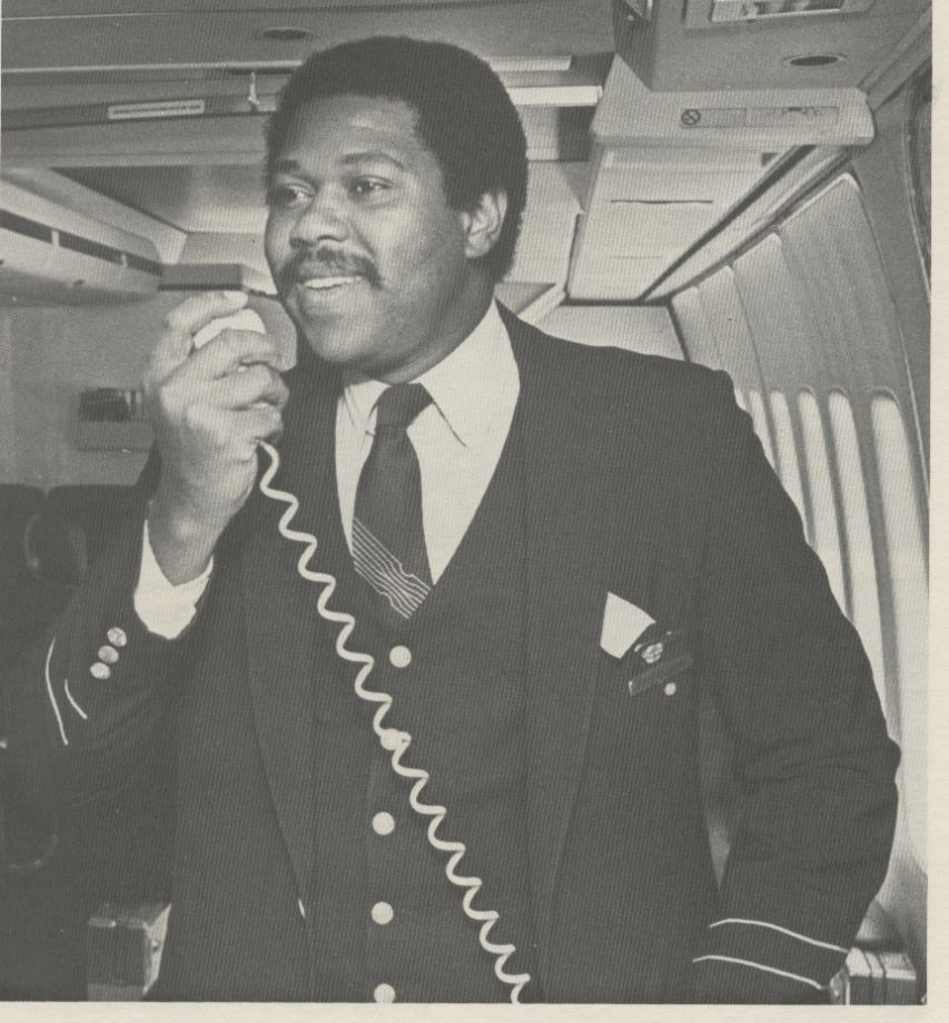 1981 Pan Am Purser Zachery Hobbs on the public address system in the first class cabin of a Boeing 747SP.