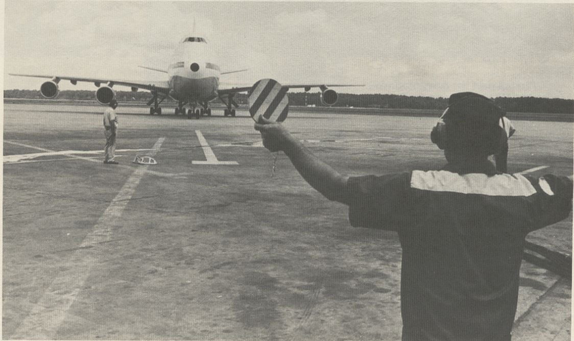 1981 A Pan Am mechanic guides a 747 to a parking area.