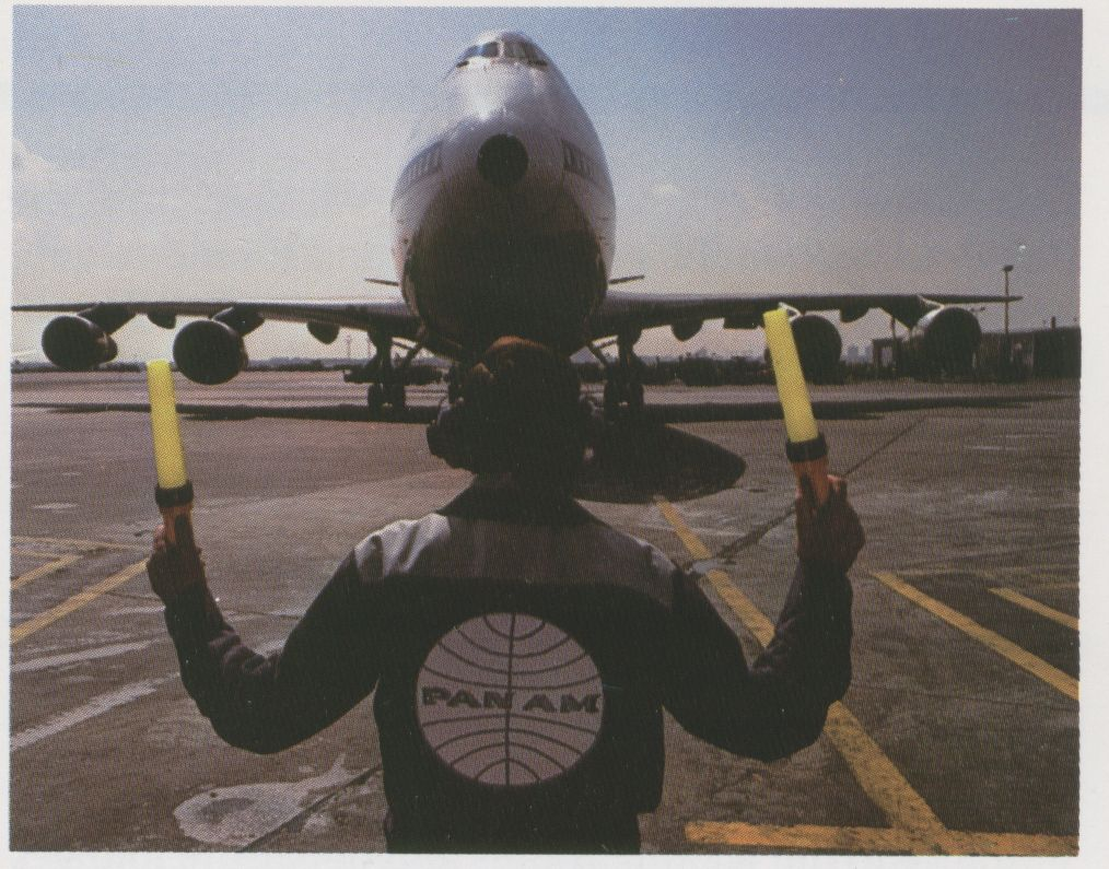 1983 April, A Pan Am Mechanic guides a 747 to a ramp parking spot.