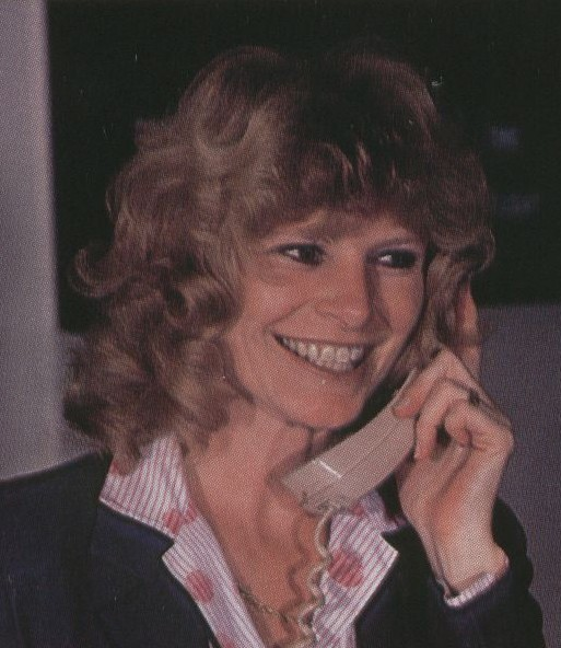1983, January, A Passenger Service Agent speaking on the phone at San Francisco Airport.  You can see the stylized Pan Am logo on her blouse.  The uniform was designed by Jean Cacharel and introduced in 1980.