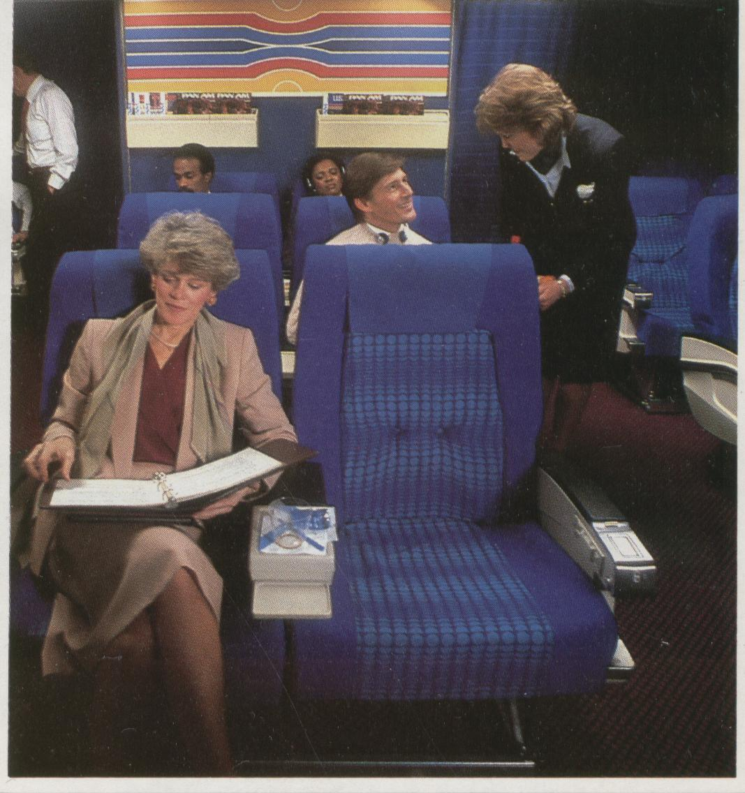 1985 When Pan Am converted the Clipper Class (Business Class) cabin from 8 across to 6 across seating bright blue seat covers were adopted as seen in this photo.  In 1988 Pan Am converted the business class  seat covers to a more demure herringbone pattern.