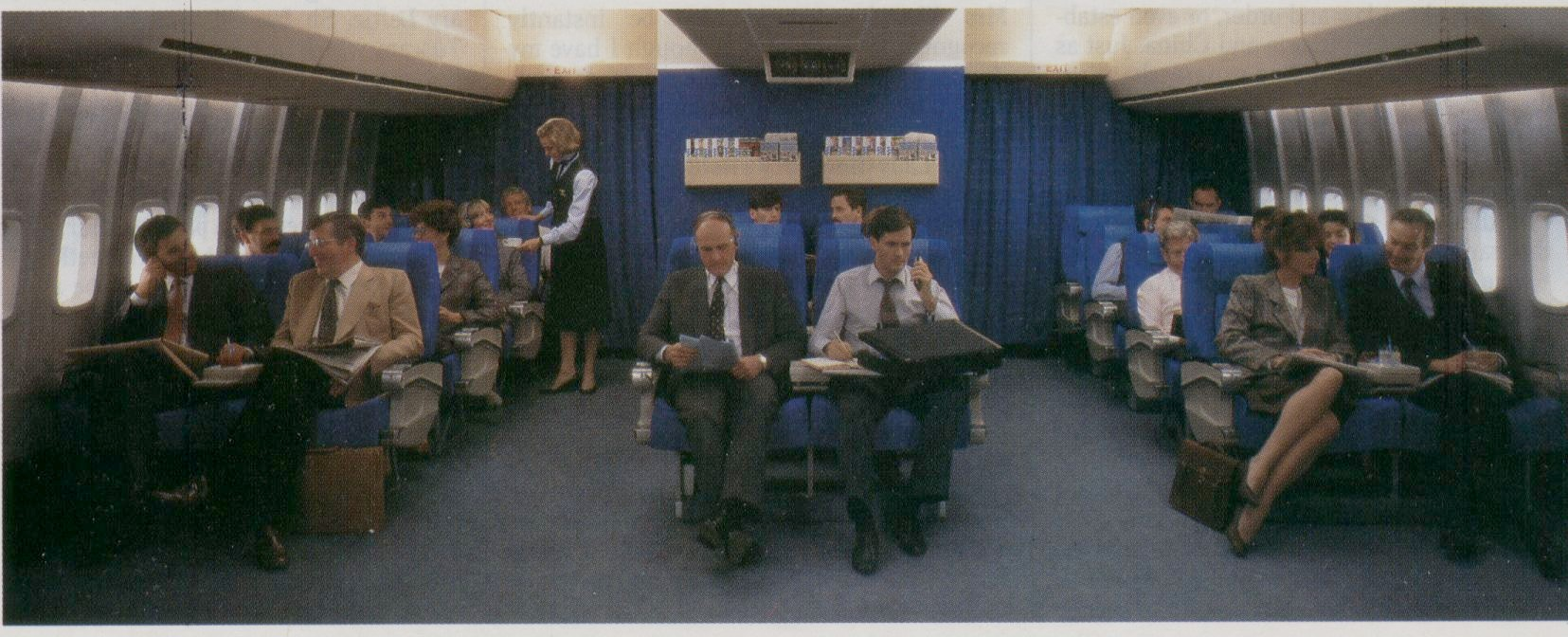 1986 When Pan Am converted the Clipper Class (Business Class) cabin from 8 across to 6 across seating bright blue seat covers were adopted as seen in this photo.  In 1988 Pan Am converted the business class  seat covers to a more demure herringbone pattern.