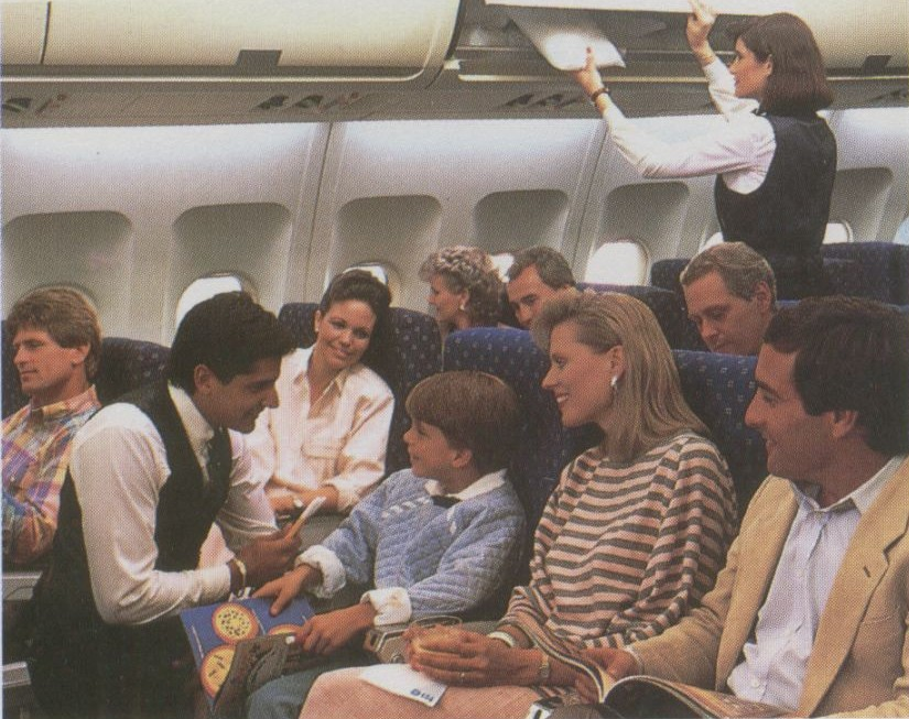 1990s Pan Am Flight Attendants assist customers in the economy cabin of an Airbus A310