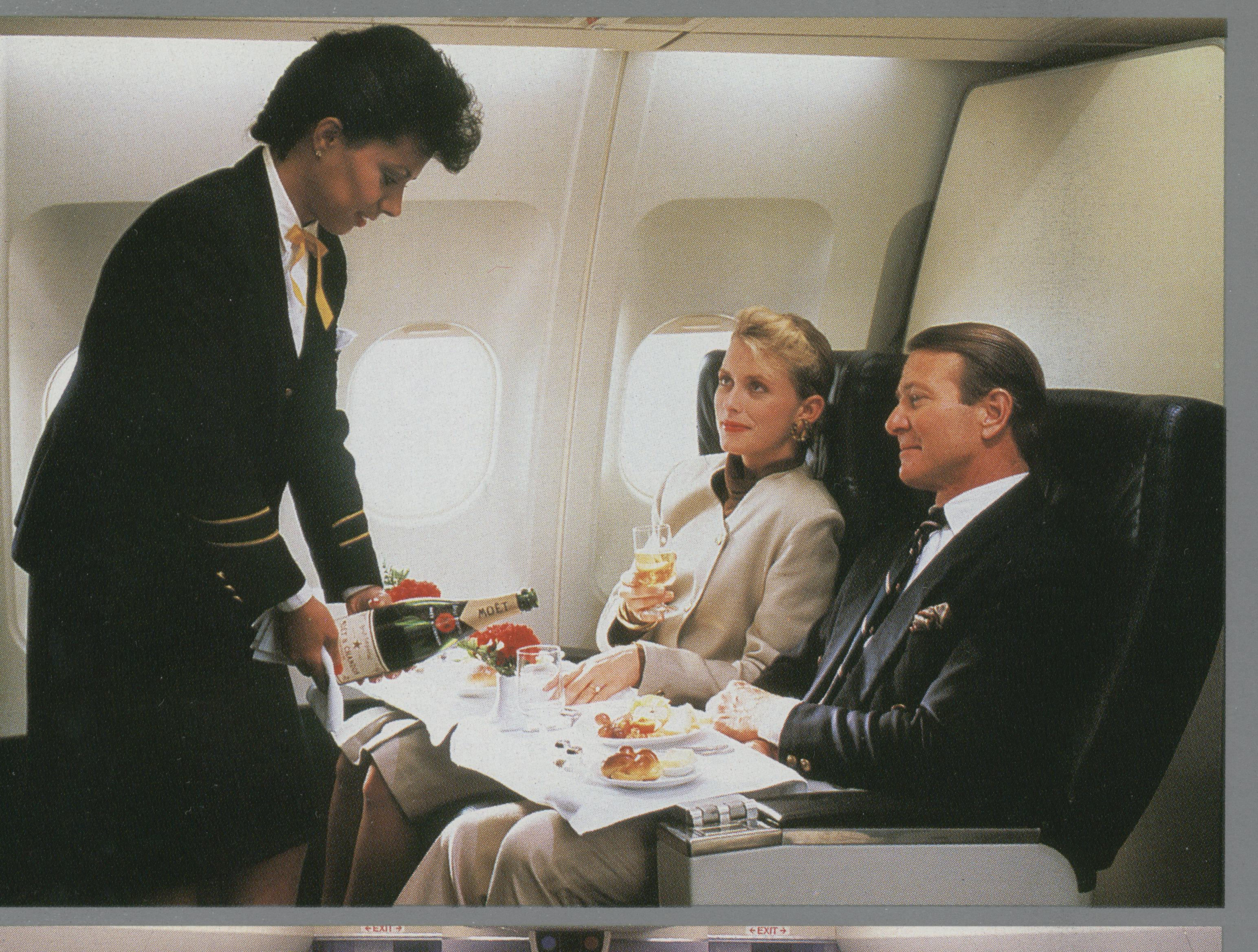 1990s A flight attendant serving customers in the First Class cabin of a Pan Am Airbus A310.  Pan Am used the long range, medium sized A310s to offer nonstop service from New York to smaller European cities such as Warsaw, Budapest, Oslo & Helsinki.