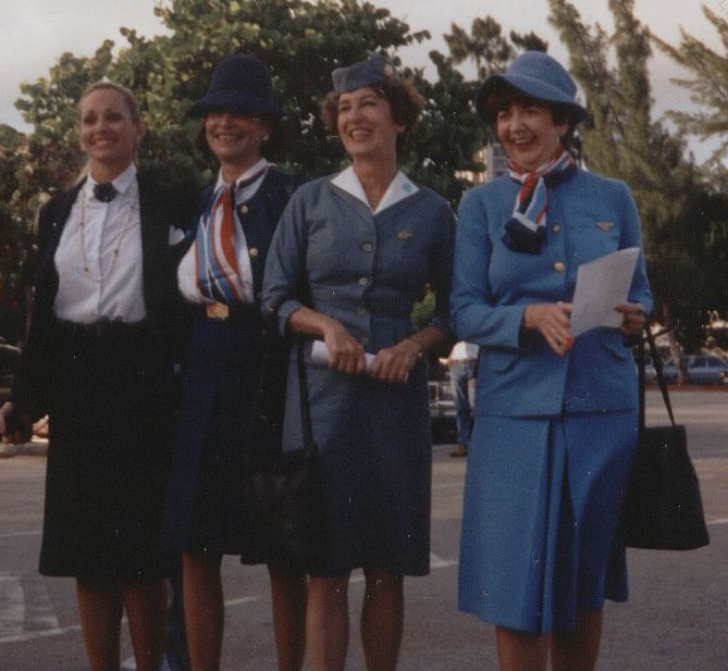1991 Three  generations of Pan Am flight attendant uniforms.  On the left is Pan Am's final uniform.  Originally designed by Adolfo in the 1980s and later modified to include the round neck tie pictured.  The 1970s Edith Head uniform with signature red, white and blue scarf is worn by the flight attendant on the right (in Pan Am blue) and second from left (Navy Blue).  The early 1960s uniform designed by Don Loper is seen on the flight attendant second from the right.