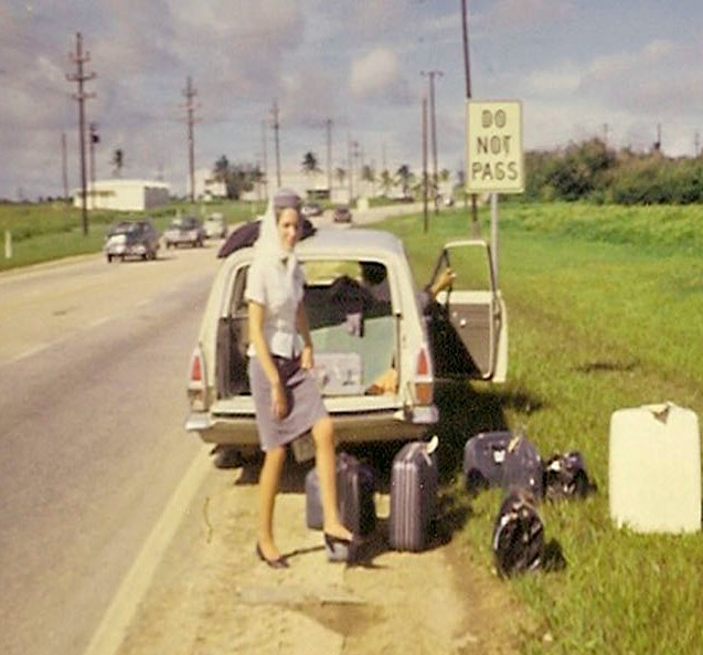 1960s Guam,  A flat tire on the crew car while en route to the airport.  The Flight Attendants begin to remove their luggage to access the spare tire.