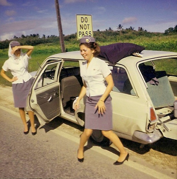 1960s Guam, Venice Fernandez and a scarf wearing colleague experience a flat tire on the crew car en route to the airport.  This candid shot is of Venice trying to flag down some help.