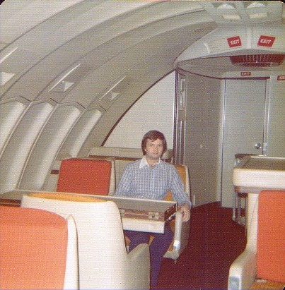 1970s A customer sitting at an unused table in the upper deck dinning room of a Pan Am 747.  The door in the back leads to the cockpit.