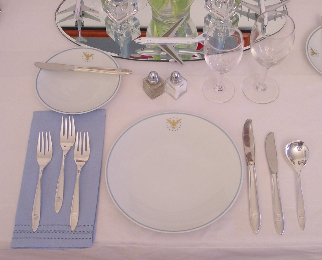 A white table cloth and blue napkin mirror the 1960s Pan Am 'President' pattern by Noritake.
