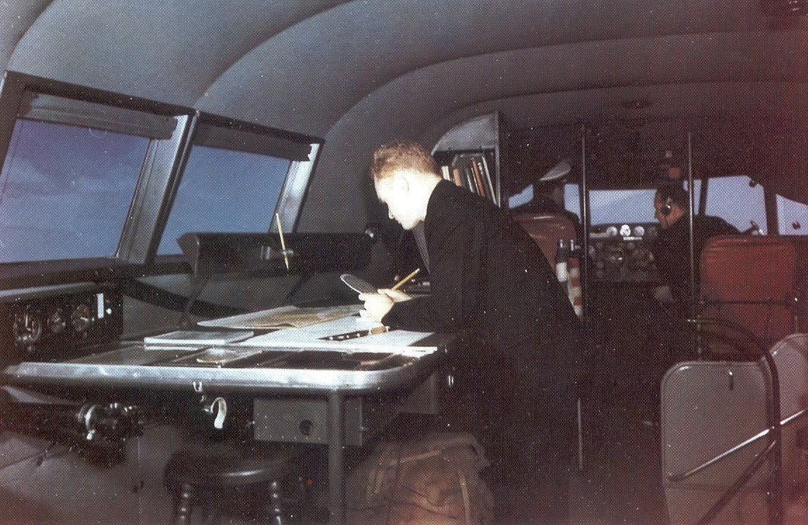 Boeing B314 Navigator at work on plotting table.  Pilot and co-pilot left and right behind the navigators right shoulder.